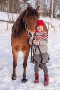 Søt lita nissejente med rød lue sammen med sin hest