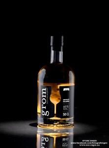 Produktfoto på svart bakgrunn av en flaske akevitt