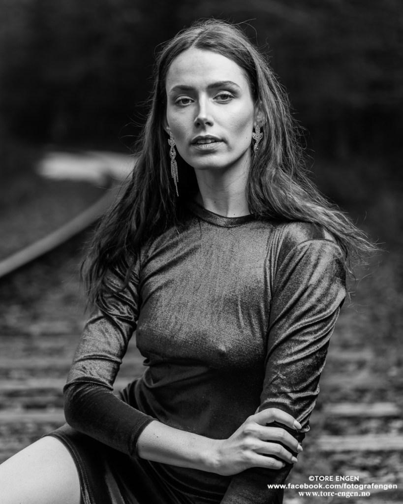 Svart-hvitt portrett av Angie på et forlatt jernbanespor