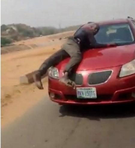 Police Officers On Top Car Bonnet