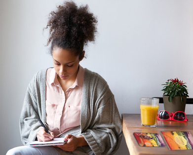 portrait of a young woman sitting at home writing on note pad