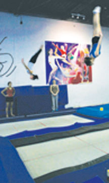 Teammates watch each other practice on the trampoline