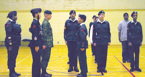 Lieutenant Bridge, in green, prepares to inspect the uniforms of the cadets before the beginning of their weekly meeting.