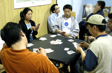 Several members of Yin's dating website are seen here playing poker at her weekly community event.
