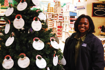 Janise Smith stands beside the Santa for Seniors Christmas tree at Value Village.