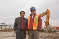Developer Hannif Highclass and site superintendent Rick Sheppard stand in front of a crane at the site of Chand Morningside Plaza. The retail plaza is to be completed by August. (Gesilayefa Azorbo/Toronto Observer)
