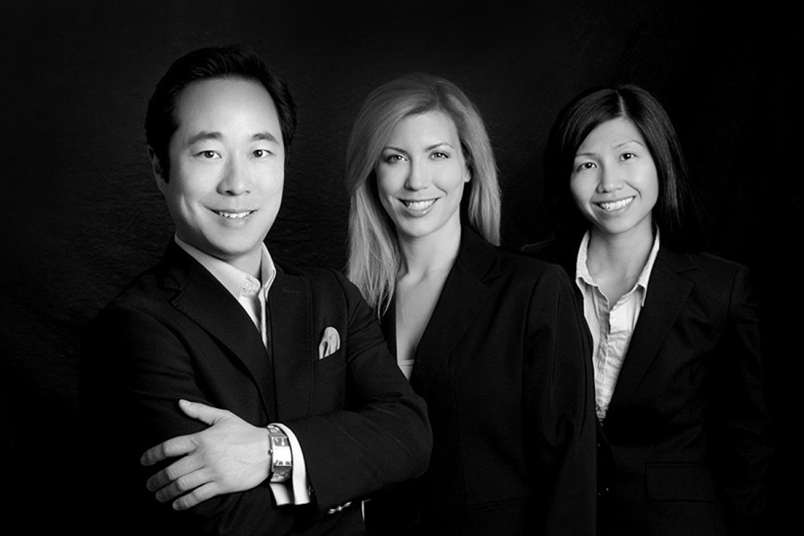 Professional headshots in black and white of three people with black background taken in portrait studio
