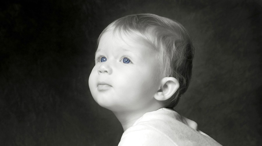 Baby portrait in black in white with blue eyes staring into space