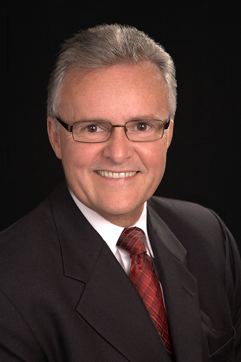 corporate portrait of man in studio with suite and red tie in portrait studio