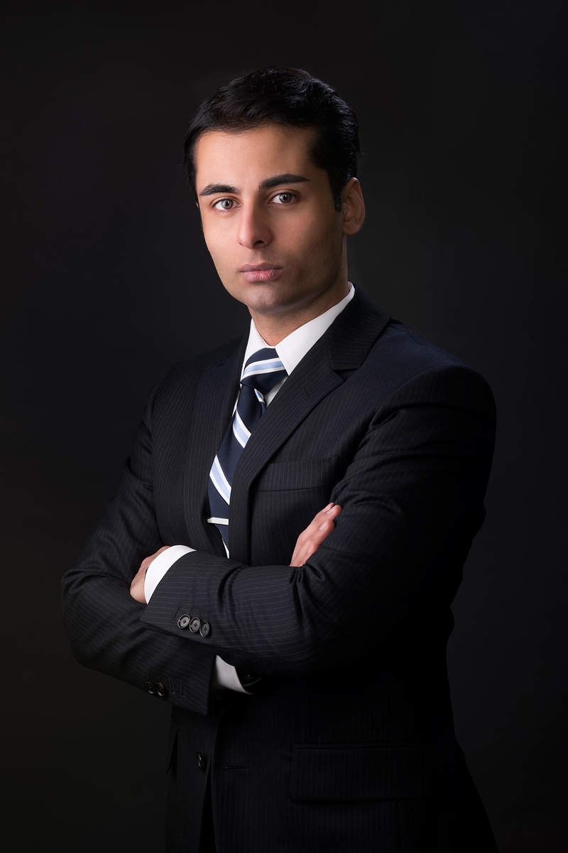 Corporate portrait of man with black suit against a black background half body shot