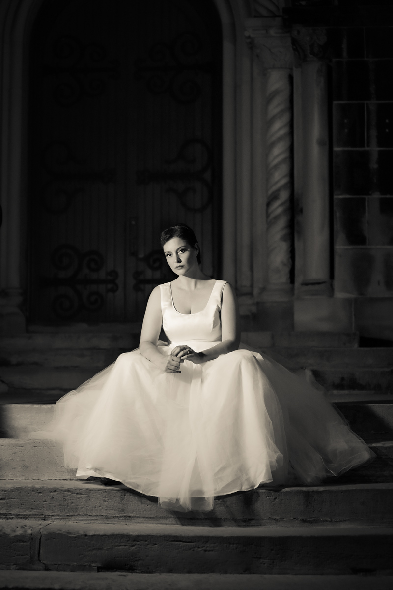 B+W wedding photo of bride sitting on steps with dark backbground