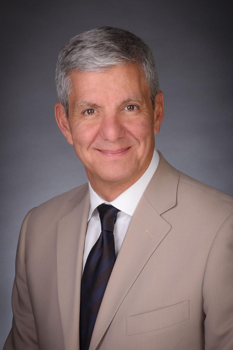 Business headshot with grey background taken in a portrait studio