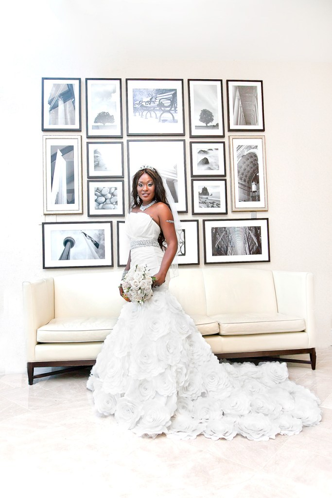 Bride standing in front of white sofa with framed pictures on the wall