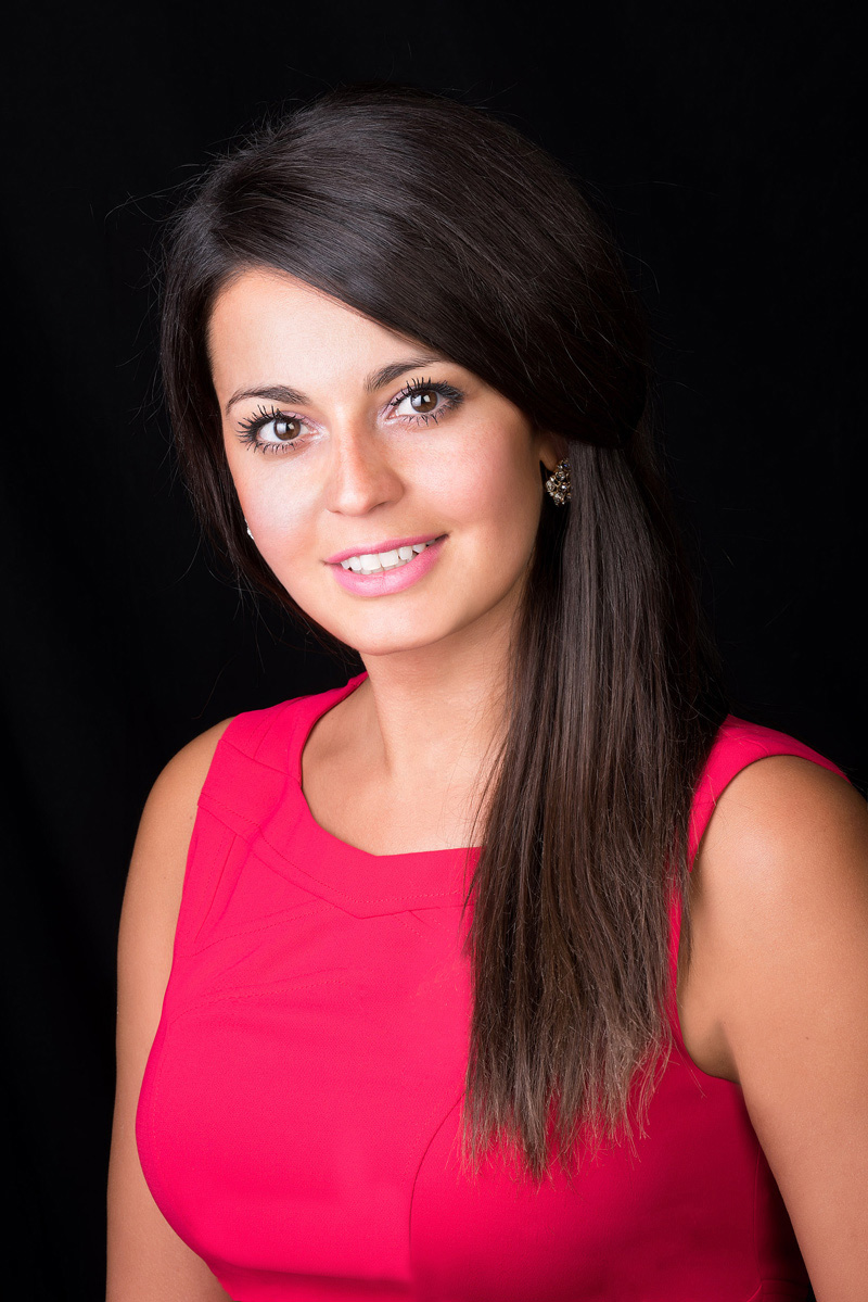 Studio headshot of a girl with a red dress and a black background taken by professional photographer