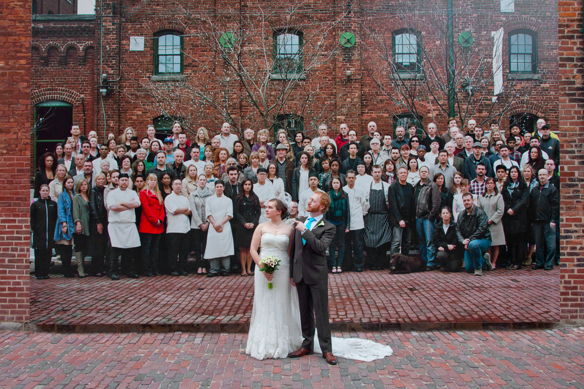 Bride and groom on cobble stone street with group of people poster behind them