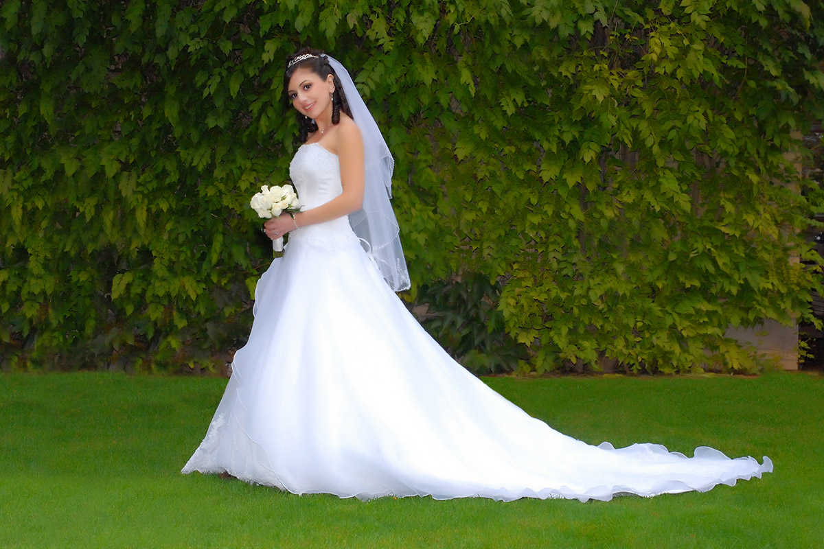 Wedding photo of bride in park with grass and leaves in background