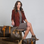 Fashion shot with women sitting on a stool with luggage in front of her.