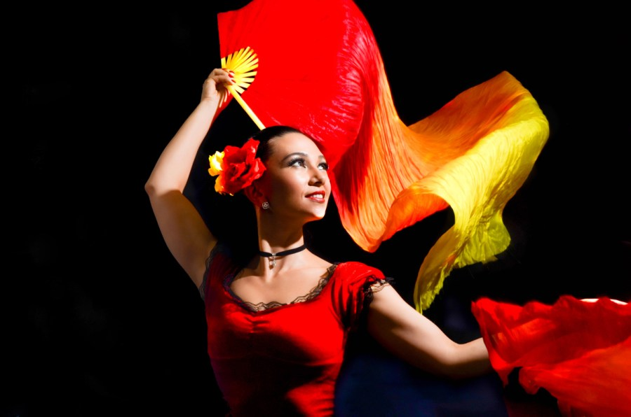 Personal branding photo of flamenco dancer holking fans with red and yellow colors.