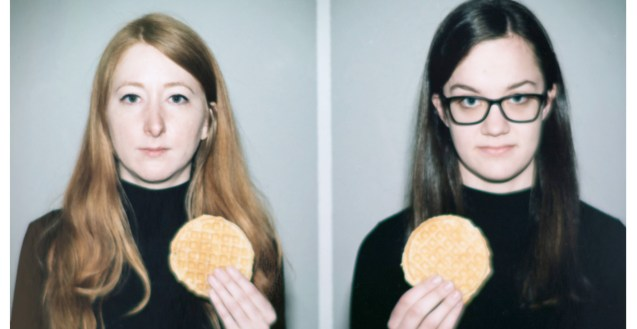 A photo of two women in black turtlenecks. One has long red hair, the other has long brown hair and glasses. They are not smiling but they are holding up ego waffles.