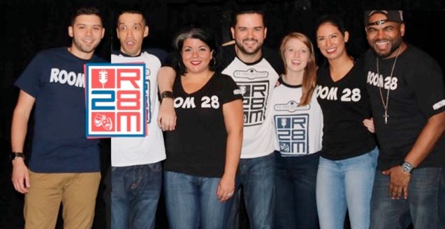 Seven members of Room 28 stand in a row to pose for this photo. They all wear Room 28 t-shirts. The blue, red and white Room 28 logo is on the left side.
