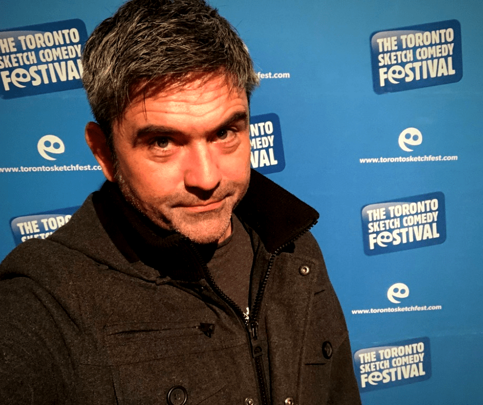 Paul Snepsts in front of a Toronto Sketch Comedy Festival step and repeat, looking fed up with the pandemic.