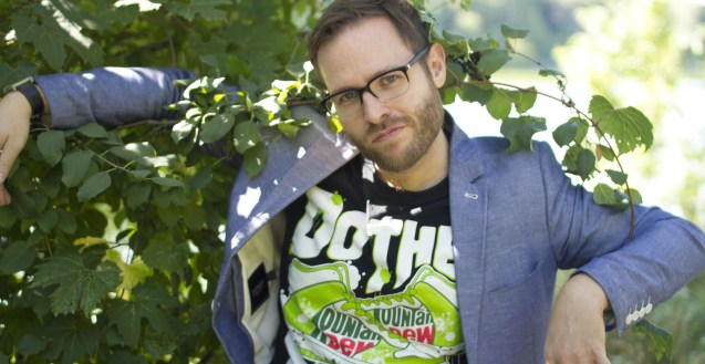Cam Wyllie, a moderately attractive man with glasses, confidently leans back into a bush that's too small to hold his weight. He is wearing a blazer and a mountain dew t-shirt.