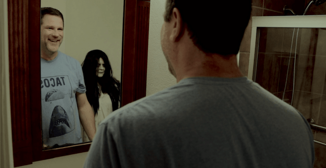 """A big goofy guy stands in front of a bathroom mirror, which shows his reflection. Also in the mirror reflection is the evil spirit from the movie, """"The Ring"""". The evil spirit is wearing a dirty nightgown, her long, tangled, black hair partially covers her face, and she is ghastly pale with dark circles under her eyes. Her intent is evil, but the guy is so lonely from isolating that he's actually happy to see her. He has a big smile on his face. The evil spirit looks confused."""