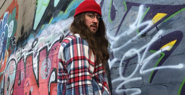 A still from the music video. Sam Roulston stands in front of a graffitied wall, with head turned to look at the camera. Sam wears hipster garb, with glasses, a long sleeved plaid shirt, red knitted hat and long brown wig.