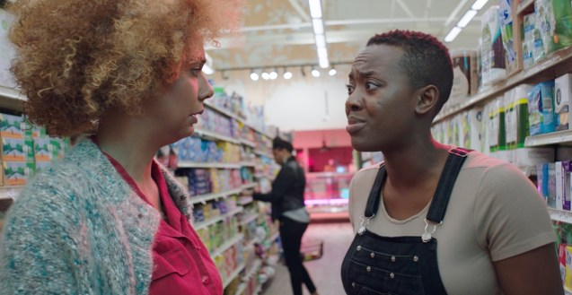 Gabby Momah (Morgan) and Carla Lee (Mary) face off in the sanitary products aisle of a grocery store. We see another customer in the background.