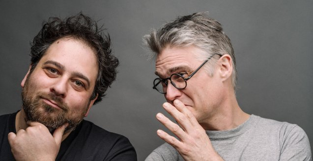 Lenny in a black t-shirt on the left side of the frame with his head tilted to the right, his hand on his bearded chin. Gavin in a grey t-shirt, on the right side of the frame, is whispering to Lenny with his hand in front of his mouth.