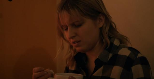 Lauren holds a cup of tea in a white mug. She looks down to read her teabag label, she looks confused.