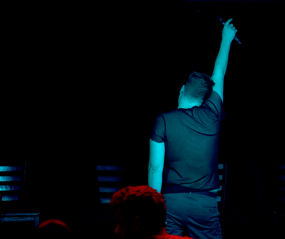 Tom Hearn on stage in dim blue light, his back to audience and his right hand in the air holding a microphone.