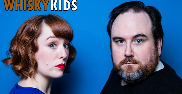"""Close up photo of Whisky Kids against a blue background, Clare Blackwood on the left, woman with red hair in a blue shirt, and Ryan F Hughes on the right, man with brown hair and a beard in a black sweater, looking over their shoulders at the viewer. In the top right corner the words """"Whisky Kids"""" in orange and white letters. Photo by Tyra Sweet"""