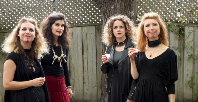 Four witches on a Wednesday afternoon. They stand looking past the camera, behind them is a tree and a wooden fence. Three of the four women have blood running down their chins.