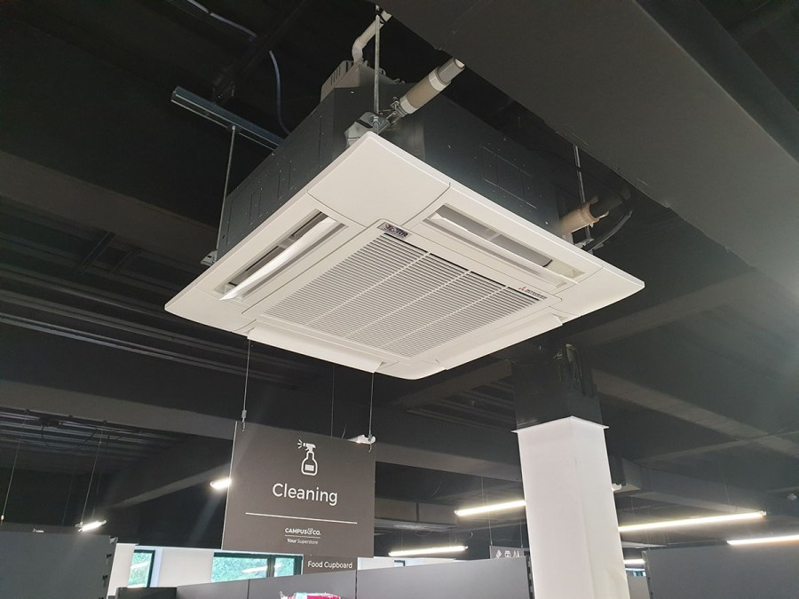 An air conditioning ceiling cassette in an open plan ceiling