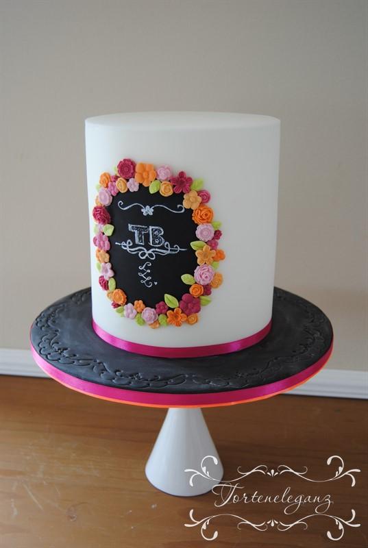 weisse Torte mit schwarzem Logo und Blumen von der seite