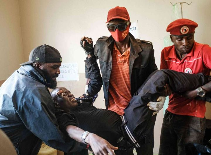 TOPSHOT - An injured man that was hit by a tear gas cannister used by police to disperce a crowd is carried into a hospital in Kayunga, Uganda on December 1, 2020. - Bobi Wine is concluding his campaign rallies  all over the country in preparation for the upcoming 2021 elections, where he will be challenging Ugandan President Yoweri Museveni, who has been in power for 35 years. (Photo by Sumy Sadurni / AFP)