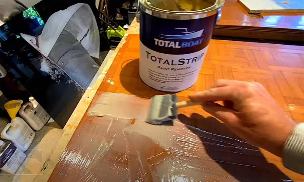 Onne van der Wal applying TotalBoat TotalStrip to remove old layers of varnish