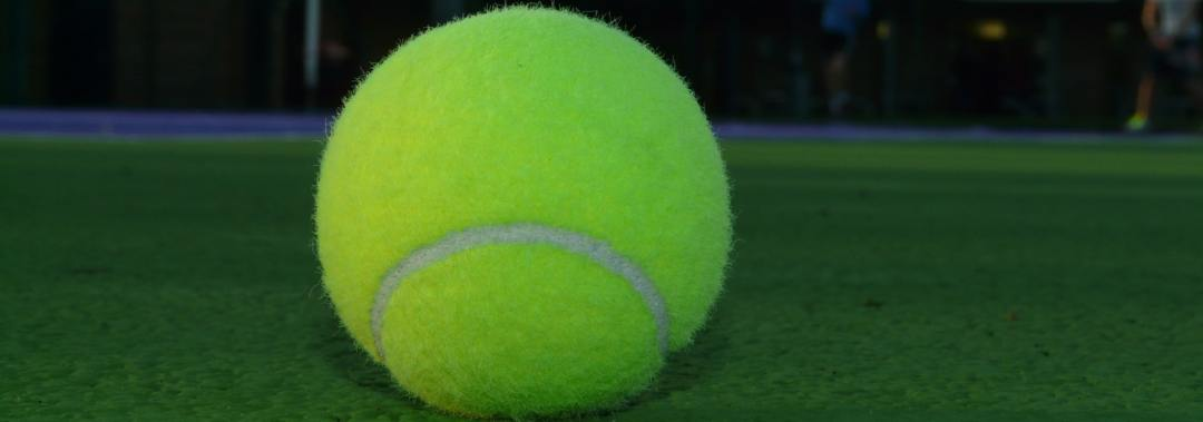 Tennis ball in the middle of court 8 with a blurred background to depict privacy