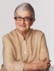A professionally shot photo of Eva Cox sitting at a table with her arms crossed as they rest on the surface of the table. She is smiling and wearing a light tan coloured long sleeved outfit; along with dark red framed eye glasses.