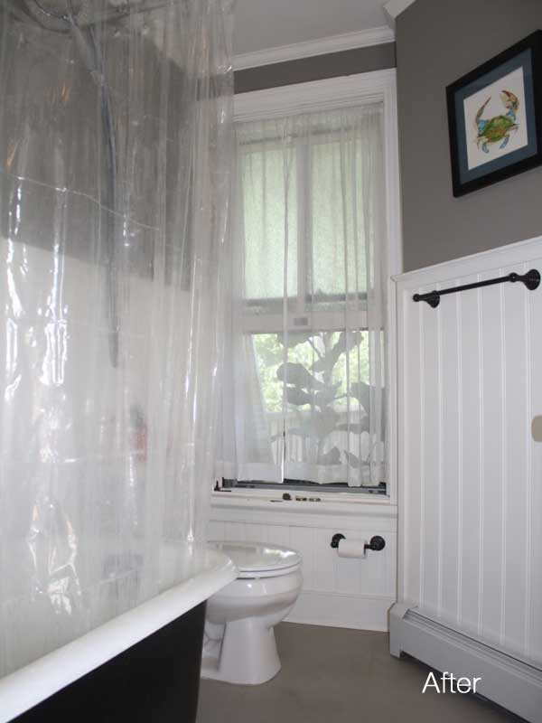 gray walls above white wainscoting in bathroom with white toilet and black painted clawfoot tub