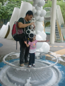 A visit in their outdoor park, Science in the Park during the middle of this year. Aria and Dad trying out the giant bubbles.