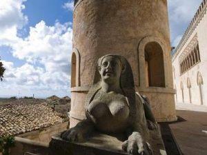 Particolare della torre del Castello di Donnafugata a Ragusa con ai piedi una statua di sfinge