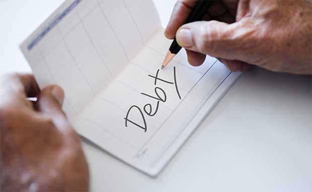 Hand writing the word Debt