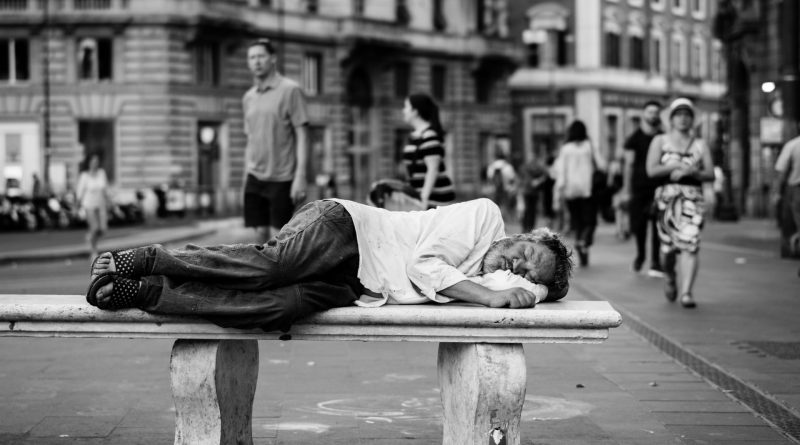 In a black and white photo a man in slightly dirty clothes sleeps on a bench. Behind him are middle-class people going for a stroll or doing their shopping. The pictures illustrates an example of inequality today.
