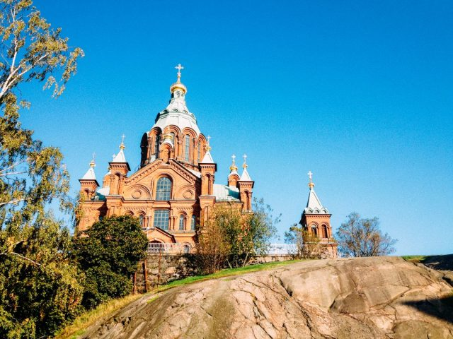 Tall Uspenski Cathedral with brick-red wall and green roof dome
