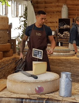 Handsome cheesemonger in port. Uniworld cruise on Towleroad and in ManAboutWorld gay travel magazine