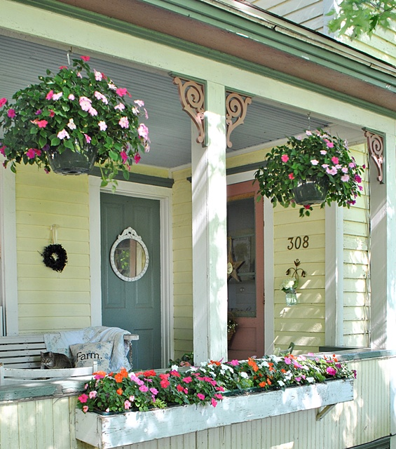 Hanging baskets on a summer farmhouse porch