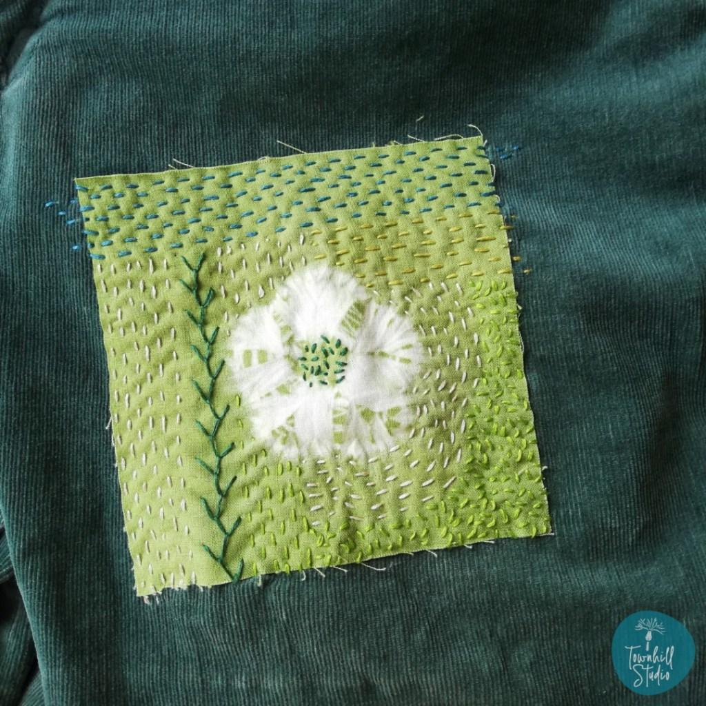 shows hand embroidered shibori flower patch on green jeans