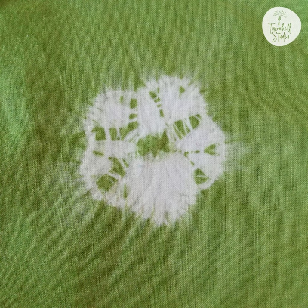 A simple shibori 5 petalled flower in green